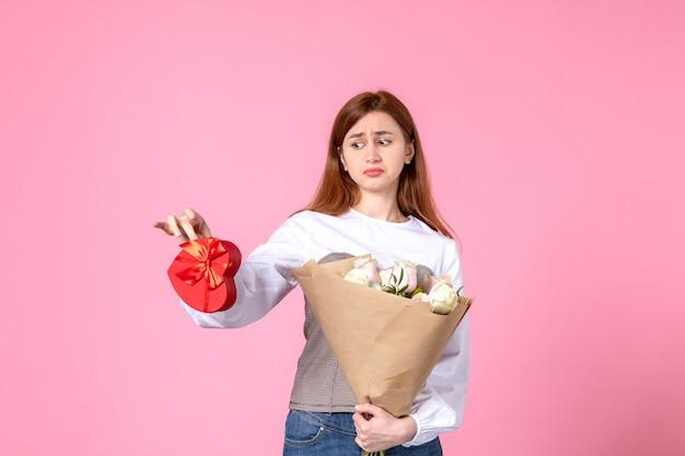 Вид спереди молодой женщины с цветами и подарком на женский день на розовом фоне, горизонтальное равенство марша, чувственное свидание, роза, женщина, любовь