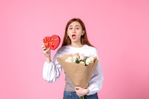 花と正面図の若い女性とピンクの背景に女性の日の贈り物として提示水平行進女性の日付の平等は官能的な女性のバラ