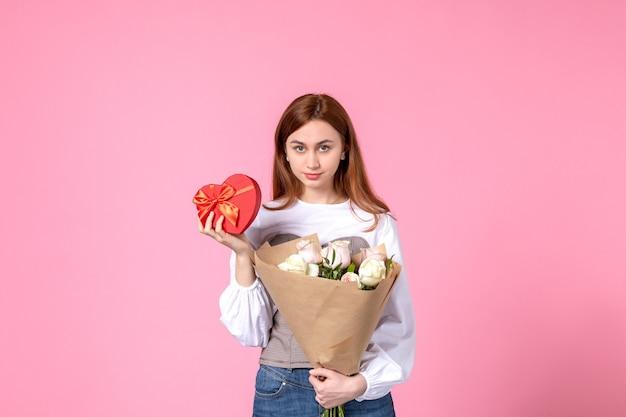 花とピンクの背景に女性の日の贈り物として提示する正面図若い女性は、水平行進フェミニンな日付の愛の官能的な平等を上昇しました