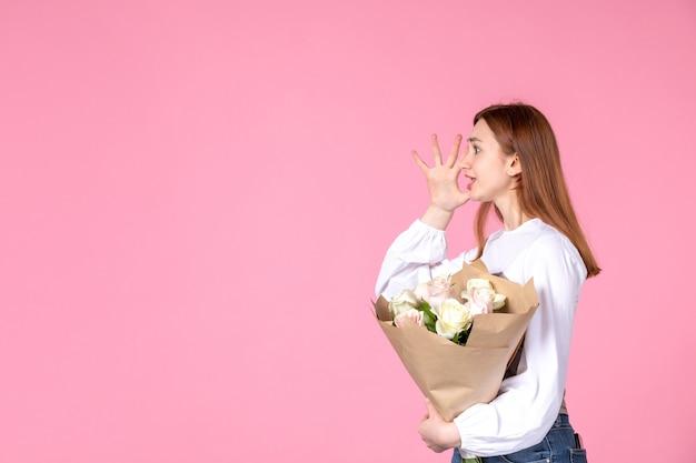ピンクの背景に女性の日として花を持つ正面図若い女性水平フェミニンな行進愛の女性官能的な日付平等が上昇しました
