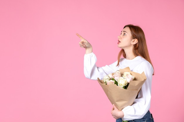 ピンクの背景に女性の日として花を持つ正面図若い女性水平フェミニン行進愛女性官能的な日付平等バラ