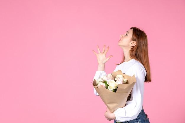 Vista frontale giovane femmina con fiori come womens giorno presente su sfondo rosa orizzontale femminile marzo amore sensuale data uguaglianza rosa