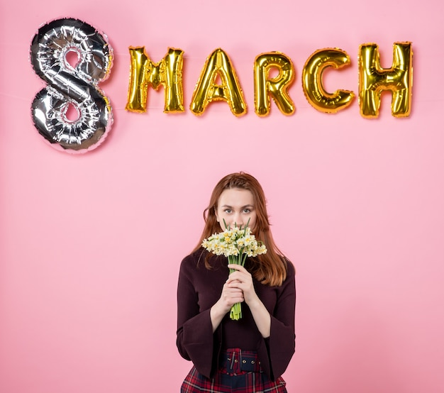 Front view young female with flowers in her hands and march decoration on pink background party womens day march marriage passion equality present