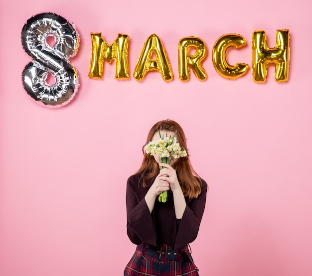 Front view young female with flowers in her hands and march decoration on pink background party womens day march marriage passion equality sensual present