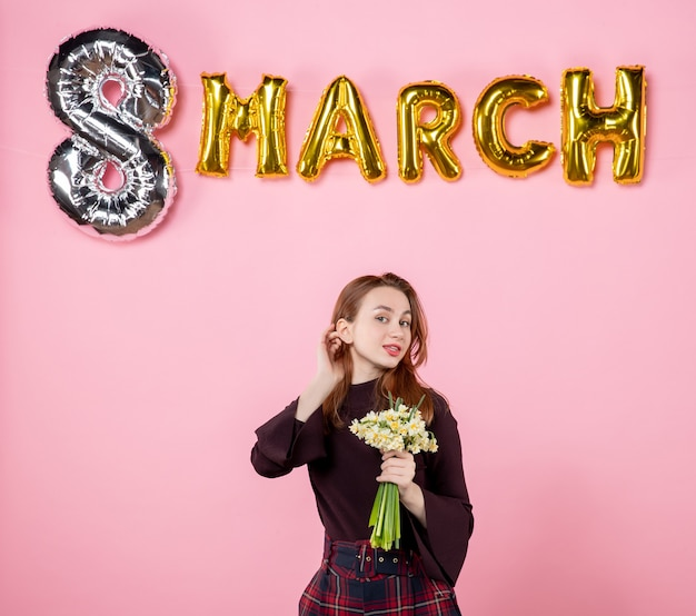 Front view young female with flowers in her hands and march decoration on pink background party womens day march passion sensual present marriage