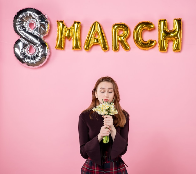 Front view young female with flowers in her hands and march decoration on pink background present womens day march marriage party equality sensual
