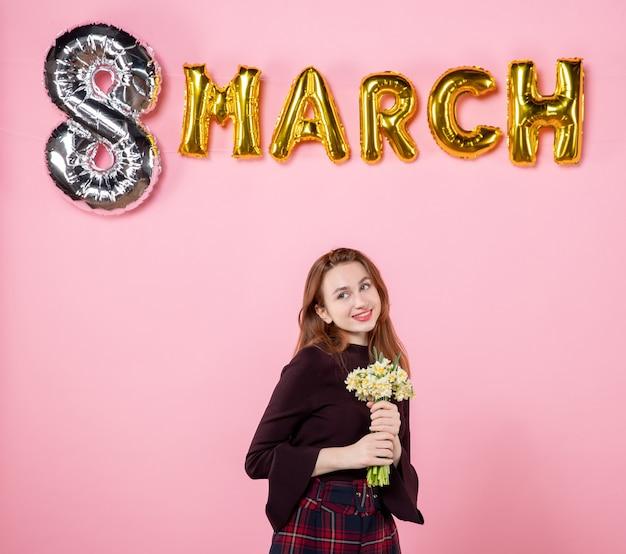 Вид спереди молодая женщина с цветами в руках и мартовским украшением на розовом фоне, вечеринка, женский день, мартовское равенство, страсть к браку, настоящее