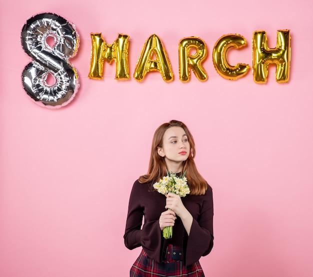 Вид спереди молодая женщина с цветами в руках и маршевым украшением на розовом фоне, вечеринка, женский день, марш, страсть, страсть, чувственное равенство