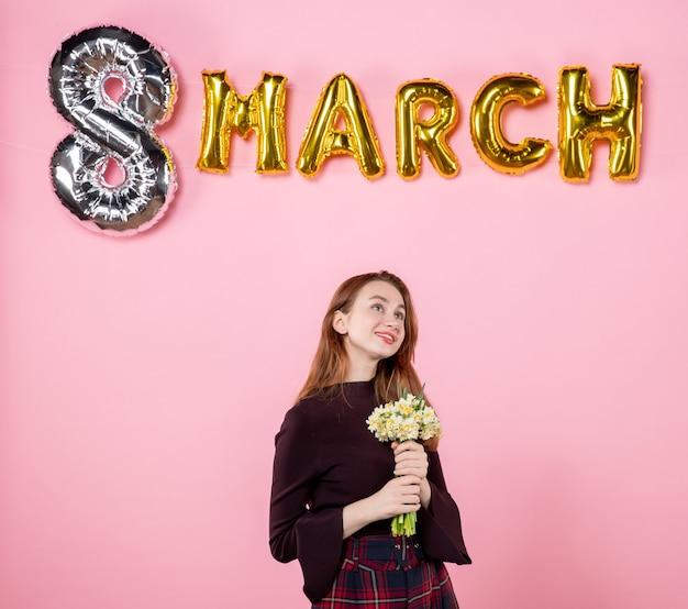 Вид спереди молодая женщина с цветами в руках и мартовским украшением на розовом фоне, вечеринка, женский день, марш, чувственная страсть к браку, настоящее