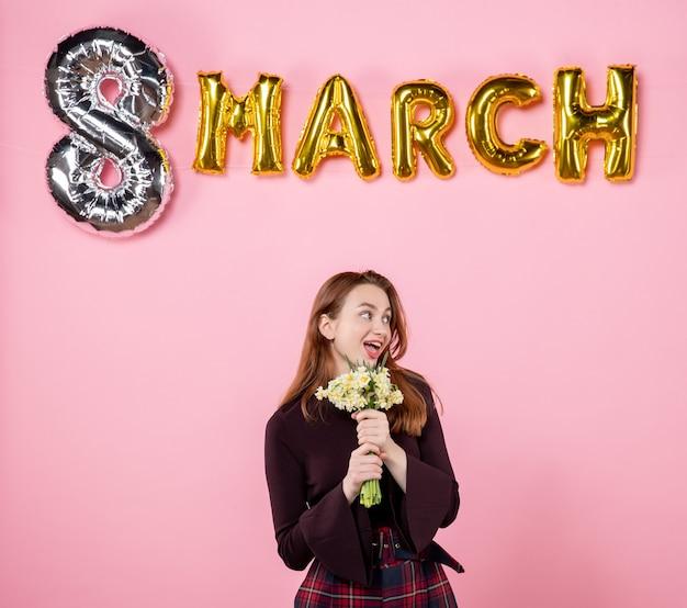 그녀의 손에 꽃과 분홍색 배경에 3 월 장식 전면보기 젊은 여성 선물 여성의 날 3 월 결혼 열정 파티 평등 관능적 인