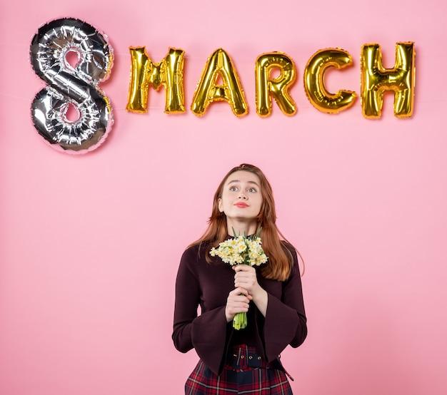 Вид спереди молодая женщина с цветами в руках и маршевым украшением на розовом фоне, настоящий женский день, марш, брак, страсть, вечеринка, равенство