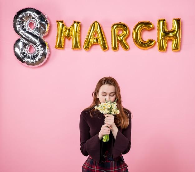그녀의 손에 꽃과 분홍색 배경에 3 월 장식 전면보기 젊은 여성 선물 여성의 날 3 월 결혼 열정 파티 관능적 인