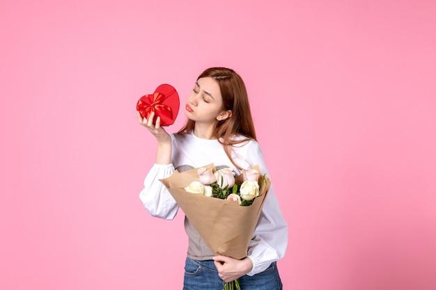 Vista frontale giovane femmina con fiori e presente come regalo di giorno delle donne su sfondo rosa parità di marcia orizzontale data femminile rosa amore sensuale