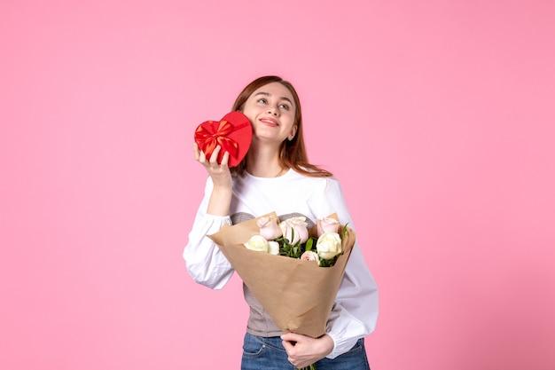 Vista frontale giovane femmina con fiori e presente come regalo di giorno delle donne su sfondo rosa parità di marcia orizzontale data femminile rosa donna amore sensuale