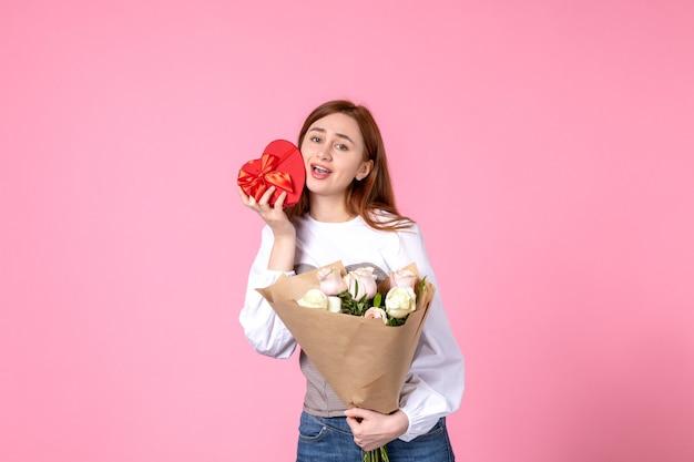 Vista frontale giovane femmina con fiori e presente come regalo di giorno delle donne su sfondo rosa parità di marcia orizzontale femminile data rose donna amore sensuale