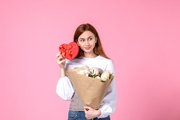 Vista frontale giovane femmina con fiori e presente come regalo di giorno delle donne su sfondo rosa parità di marcia orizzontale amore femminile data rosa donna