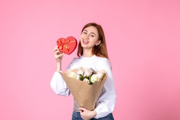 Vista frontale giovane femmina con fiori e presente come regalo di giorno delle donne su sfondo rosa parità di marcia orizzontale amore sensuale data femminile rosa donna
