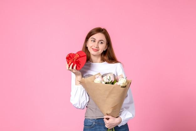 Vista frontale giovane femmina con fiori e presente come regalo di giorno delle donne su sfondo rosa marcia orizzontale uguaglianza sensuale data femminile rosa amore