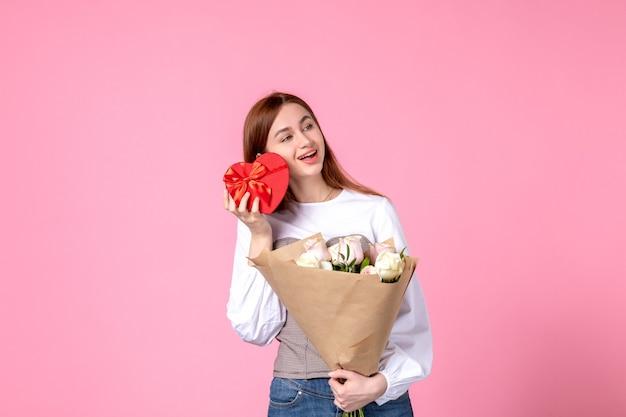Giovane donna di vista frontale con fiori e presente come regalo di giorno delle donne su sfondo rosa donna di rosa data femminile sensuale di uguaglianza marcia orizzontale sfondo rosa