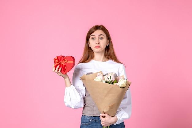 Giovane femmina di vista frontale con i fiori e presente come regalo di giorno delle donne su fondo rosa amore della donna data femminile sensuale di uguaglianza orizzontale di marzo