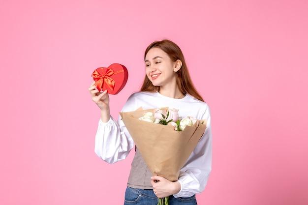Vista frontale giovane femmina con fiori e presente come regalo di giorno delle donne su sfondo rosa orizzontale marzo donna data uguaglianza rosa amore femminile
