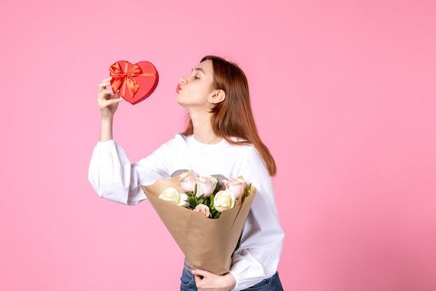 Vista frontale giovane femmina con fiori e presente come regalo di giorno delle donne su sfondo rosa marcia orizzontale uguaglianza donna amore data femminile rosa