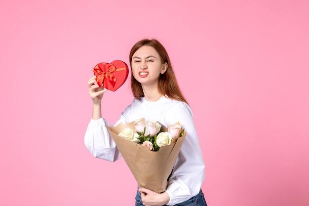 Vista frontale giovane femmina con fiori e presente come regalo di giorno delle donne su sfondo rosa marcia orizzontale uguaglianza donna amore data sensuale rosa