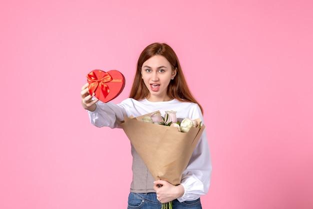 Vista frontale giovane femmina con fiori e presente come regalo di giorno delle donne su sfondo rosa marcia orizzontale uguaglianza donna amore sensuale data femminile rosa