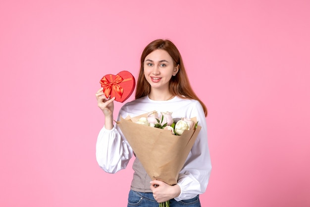 Vista frontale giovane femmina con fiori e presente come regalo di giorno delle donne su sfondo rosa marcia orizzontale uguaglianza donna rosa amore sensuale data femminile