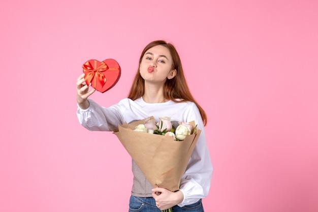 Vista frontale giovane femmina con fiori e presente come regalo di giorno delle donne su sfondo rosa marcia orizzontale donna amore sensuale data femminile rosa