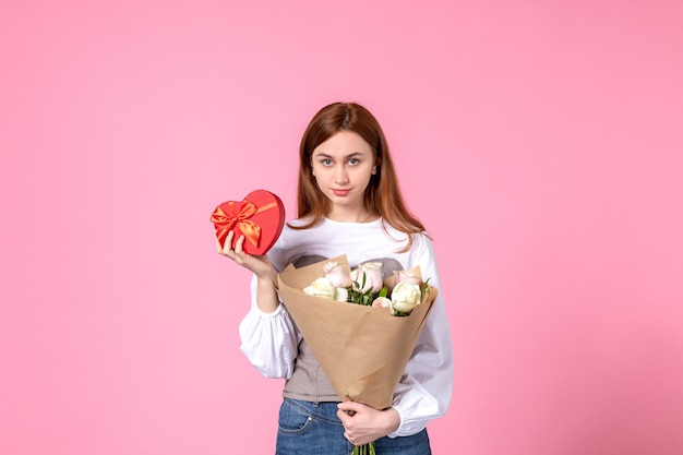 Vista frontale giovane femmina con fiori e presente come regalo di giorno delle donne su sfondo rosa rosa marcia orizzontale data femminile amore sensuale uguaglianza