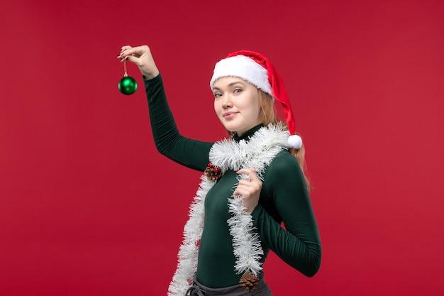 Вид спереди молодая женщина с гирляндами и новогодним настроением на красном фоне
