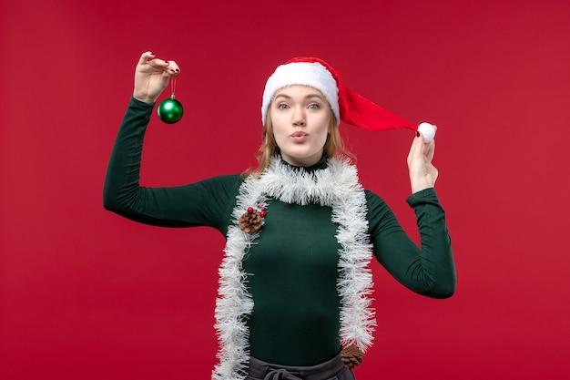 Вид спереди молодая женщина с гирляндами, держащая игрушку на красном фоне