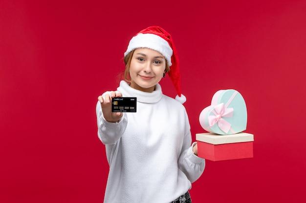 빨간 책상에 선물 및 은행 카드와 전면보기 젊은 여성