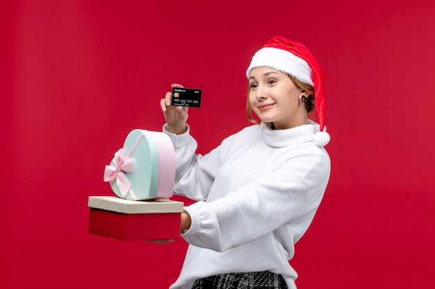 Front view young female with gifts and bank card on a red background