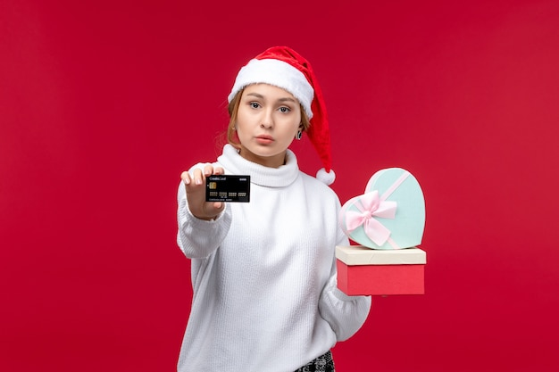 Front view young female with gifts and bank card on the red background