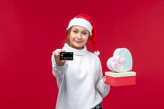Front view young female with gifts and bank card on red desk
