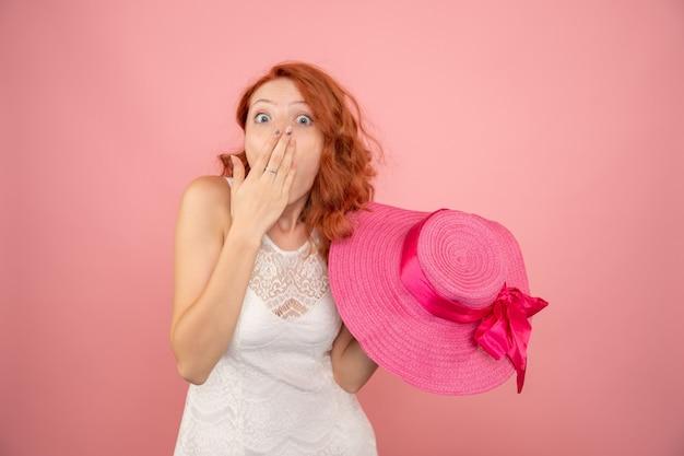 Vista frontale della giovane donna con il suo cappello rosa sulla parete rosa