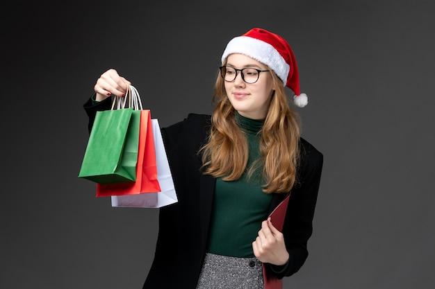 暗い壁の新年の贈り物のクリスマスに休日のプレゼントと正面図若い女性