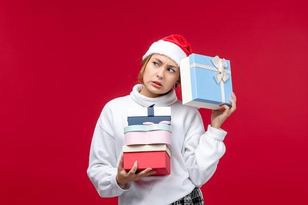 Вид спереди молодая женщина с праздничными подарками на красном фоне