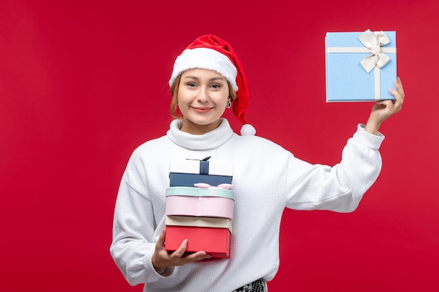 赤い机の上に休日のプレゼントと正面図若い女性