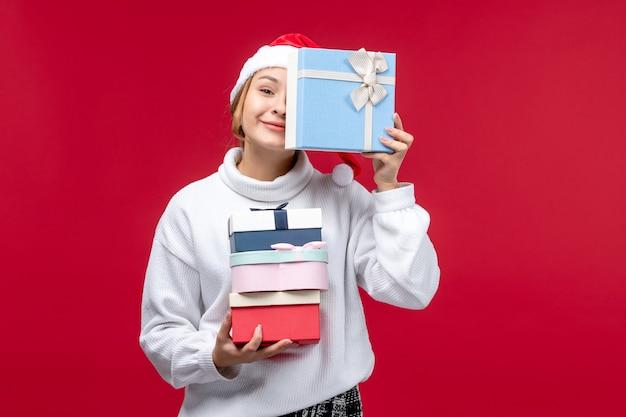 Giovane donna di vista frontale con regali di festa su uno sfondo rosso