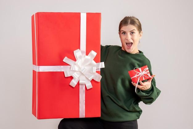 Вид спереди молодая женщина с маленькими и огромными рождественскими подарками