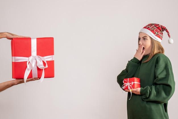 プレゼントがほとんどなく、男性から他の贈り物を受け取っている正面図の若い女性