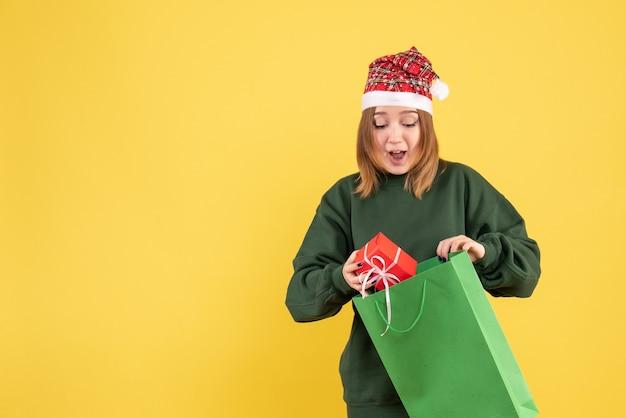 Вид спереди молодая женщина с небольшим подарком
