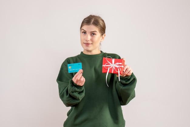 小さなクリスマスプレゼントと銀行カードを持つ正面図若い女性