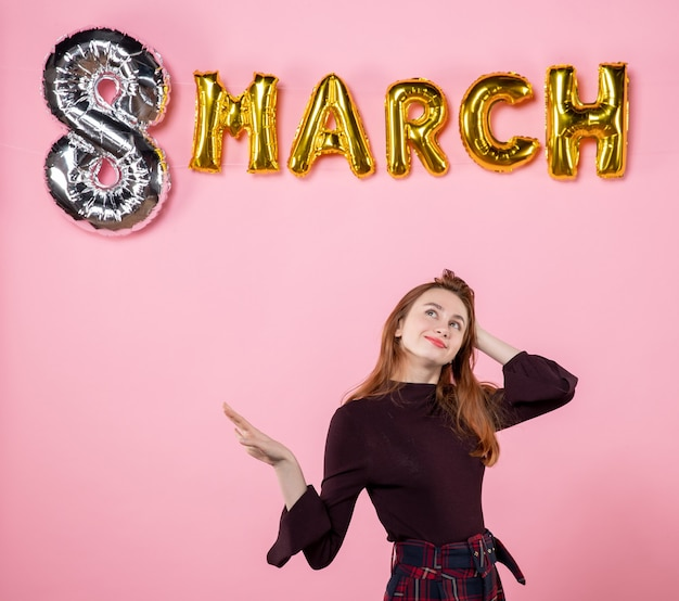 ピンクの背景に3月の装飾が施された正面図若い女性官能的な結婚カップルギフト女性の日情熱平等色が存在します