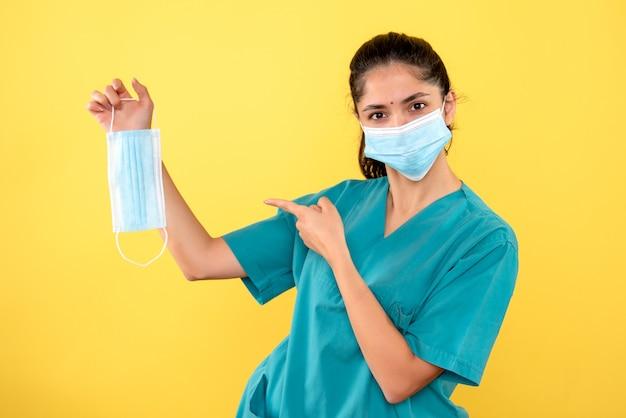 Vista frontale della giovane donna con maschera medica che punta alla maschera in mano sulla parete gialla