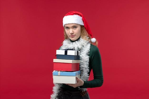 赤い背景に新年のプレゼントと正面図若い女性