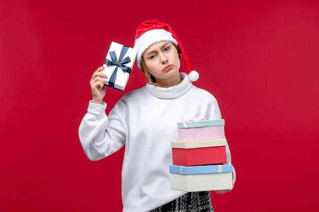 赤い机の上に新年のプレゼントと正面図若い女性